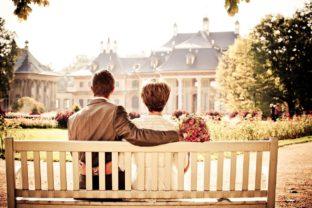 זוג יושבים יחד על ספסל בצבע לבן